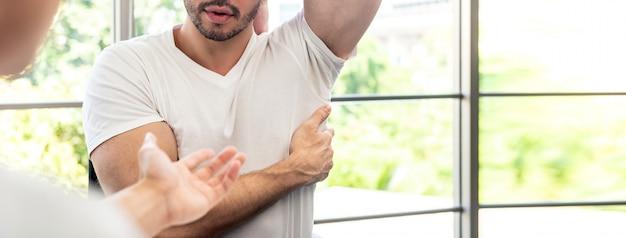 Atlety męski cierpliwy konsultować z lekarką w klinice o mięśnia bólu