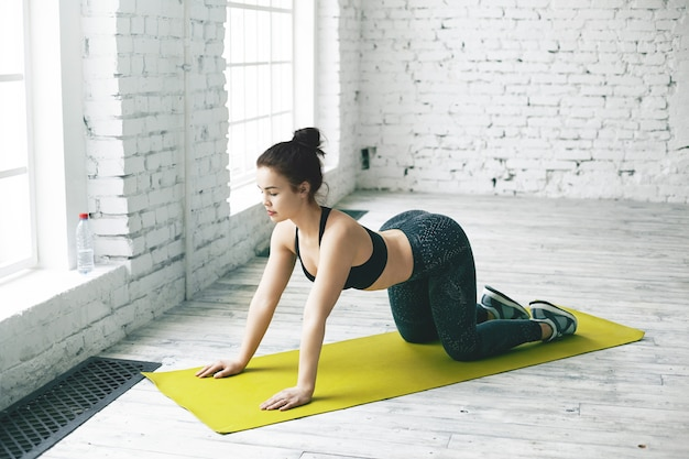 Atletyczna młoda joginka w modnym czarnym stroju sportowym rozgrzewa kręgosłup, robi asanę krowy. elastyczna dziewczyna praktykuje wygięcia jogi w przestronnym pokoju z białą cegłą na ścianę miejsca na tekst
