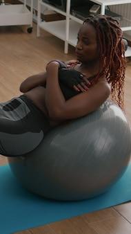 Atletyczna młoda kobieta robi poranny trening fitness w salonie, wykonując mięśnie brzucha, siedząc na szwajcarskiej piłce jogi