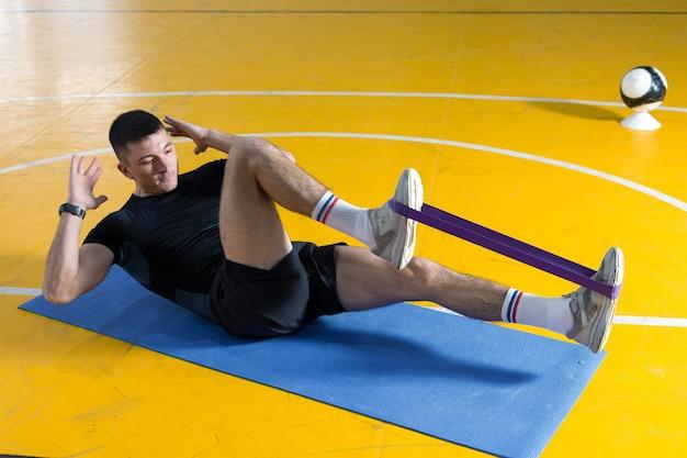 Atletyczny facet w sportowej i fitness tracker robi ćwiczenia w siłowni.
