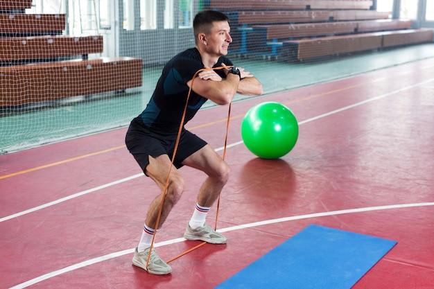 Atletyczny Facet W Sportowej I Fitness Tracker Robi ćwiczenia W Siłowni. Premium Zdjęcia