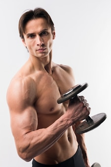 Atletyczny mężczyzna z umięśnionym ciałem trzyma ciężary