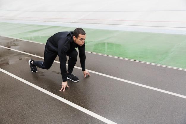 Atletyczny silny sportowiec w dresie ćwiczący podczas treningu na stadionie po deszczu