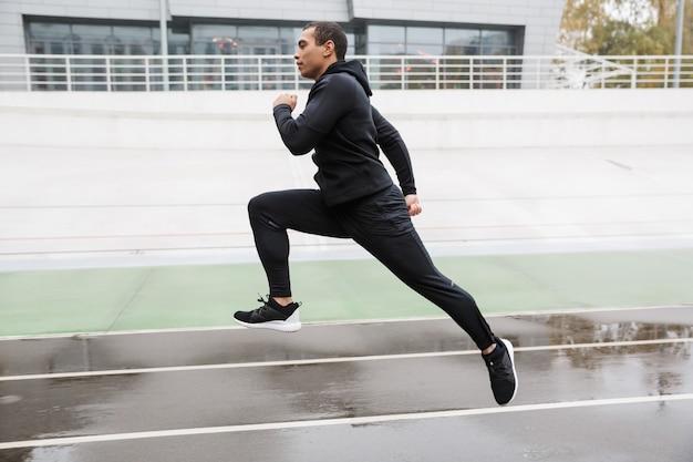 Atletyczny silny sportowiec w dresie skaczący podczas treningu na stadionie po deszczu