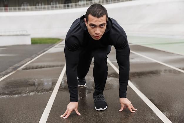 Atletyczny sportowiec kaukaski w dresie ćwiczący podczas treningu na stadionie po deszczu