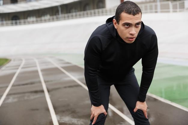 Atletyczny sportowiec kaukaski w dresie stojący podczas treningu na stadionie po deszczu