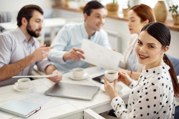 Atmosfera pracy. atrakcyjny alert ciemnowłosa młoda kobieta uśmiecha się i pije kawę, a jej koledzy rozmawiają w tle