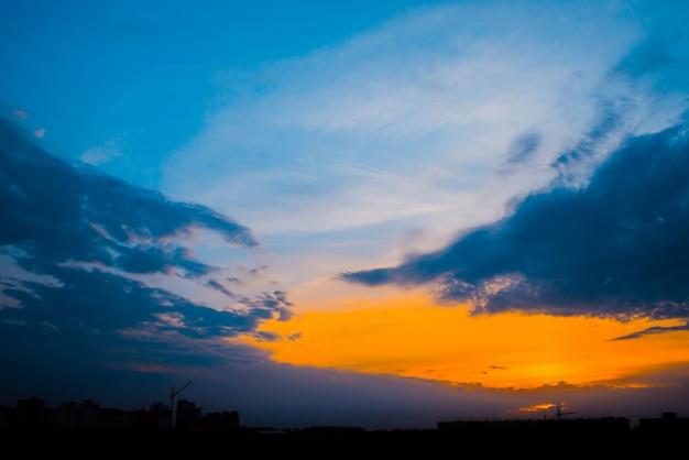 Atmosferyczne błękitne niebo pochmurne za sylwetkami budynków miasta
