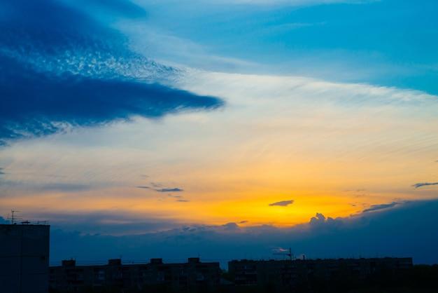 Atmosferyczne błękitne pochmurne niebo za sylwetkami budynków miasta. kobaltowo-pomarańczowe tło wschodu słońca z gęstymi chmurami