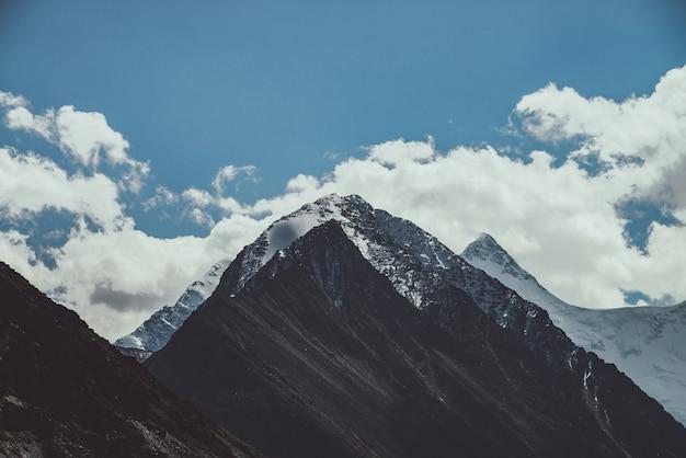 Atmosferyczny górski krajobraz z wielkim ośnieżonym szczytem i śnieżnym spiczastym szczytem w niskich chmurach w ciemnych kolorach. ponura górska sceneria z wysokim ośnieżonym szczytem pod zachmurzonym niebem w wyblakłych odcieniach.