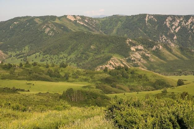 Atmosferyczny górski zielony krajobraz o świcie słonecznym. w oddali widać wiele warstw gór.
