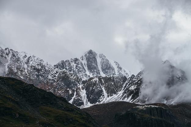Atmosferyczny krajobraz alpejski z wielką górą szczytową ze śniegiem w niskich chmurach. dramatyczna górska sceneria z ostrym szczytem w pochmurną pogodę. niesamowity widok na śnieżny spiczasty szczyt w zachmurzonym niebie.