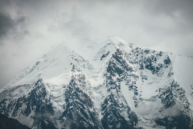Atmosferyczny krajobraz gór z dużym śnieżnym szczytem górskim z gzymsami śnieżnymi w niskich chmurach. niesamowita minimalistyczna sceneria ze śnieżnobiałym wysokim szczytem w pochmurną pogodę. gigantyczne górskie ściany w chmurach.