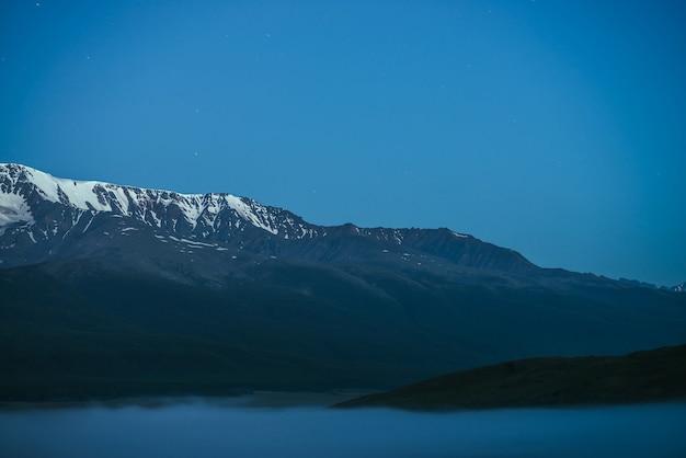 Atmosferyczny krajobraz gór z gęstą mgłą i wielkim pasmem górskim śniegu pod zmierzchem. alpejskie krajobrazy z dużym śnieżnym grzbietem górskim nad gęstą mgłą w nocy. ośnieżone skały nad chmurami o zmierzchu.