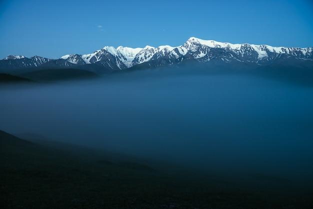 Atmosferyczny krajobraz gór z gęstą mgłą i wielkim śniegiem na szczycie góry pod zmierzchem. alpejskie krajobrazy z dużymi ośnieżonymi górami nad gęstą mgłą w nocy. wysoki szczyt śniegu nad chmurami w zmierzchu.