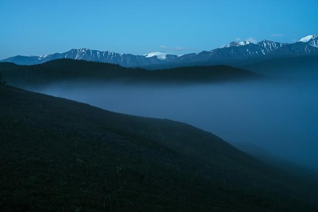 Atmosferyczny krajobraz gór z gęstą mgłą i wspaniałym szczytem śniegu pod zmierzchem. alpejskie krajobrazy z dużymi ośnieżonymi górami nad gęstą mgłą w nocy. wysoki szczyt śniegu nad chmurami w zmierzchu.