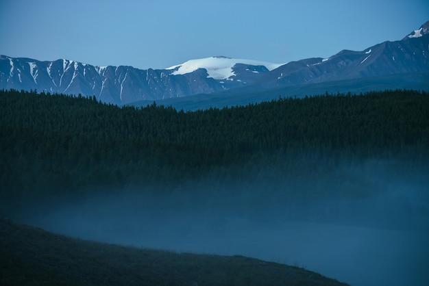 Atmosferyczny krajobraz gór z gęstą mgłą i wspaniałym szczytem śniegu pod zmierzchem.