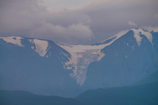 Atmosferyczny krajobraz gór z wielkim lodowcem na szczycie góry olbrzymów nad lasem we mgle wcześnie rano. minimalna alpejska sceneria z piękną, wysoką, śnieżną ścianą górską we mgle pod zachmurzonym niebem.