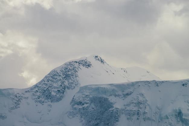 Atmosferyczny krajobraz góralski z wysokimi śnieżnymi górskimi ścianami pod zachmurzonym niebem. dramatyczna sceneria z pokrytym śniegiem szczytem góry w pochmurną pogodę. światło słoneczne przez chmury nad szczytem śniegu.
