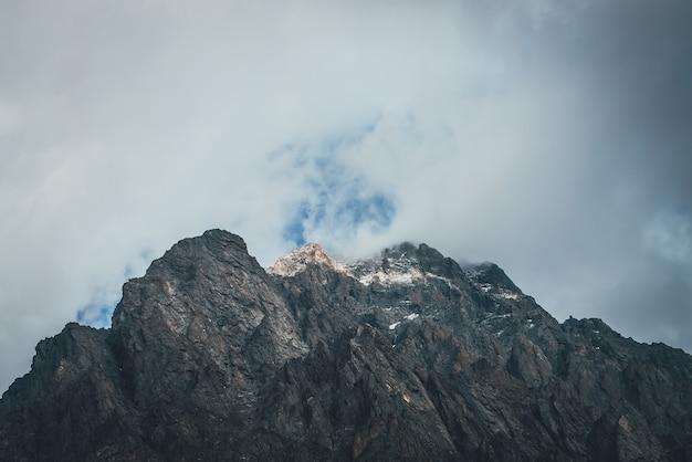 Atmosferyczny krajobraz górski z niską chmurą na szczycie góry w słońcu. ciemne skały ze śniegiem i niebieskim świetlikiem na szarym pochmurnym niebie. piękna górska sceneria z niską chmurą na skalistym szczycie w słońcu