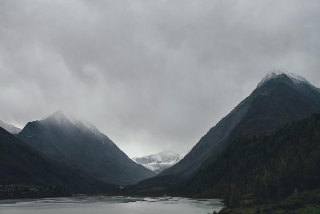 Atmosferyczny krajobraz górski z szarym górskim jeziorem wśród ciemnych skał ze śniegiem pod szarym pochmurnym niebem. dramatyczna górska sceneria z alpejskim jeziorem w pochmurną pogodę. ponury widok na góry w dolinie.