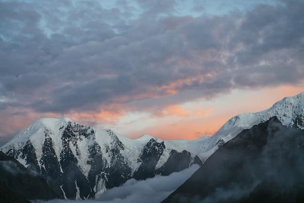 Atmosferyczny krajobraz górski z wielkimi ośnieżonymi górami i niskimi chmurami w dolinie pod zachmurzonym niebem fioletowy pomarańczowy świt. niesamowita alpejska sceneria z gęstą mgłą w górskiej dolinie o zachodzie lub wschodzie słońca