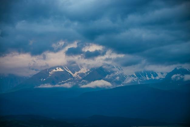 Atmosferyczny krajobraz górski z wielkimi ośnieżonymi górami w niskich chmurach i zachmurzonym niebie zachmurzeniem słońca. niesamowita minimalna alpejska sceneria z dużym lodowcem na wysokim grzbiecie górskim w niskich chmurach w niebiesko-białych kolorach