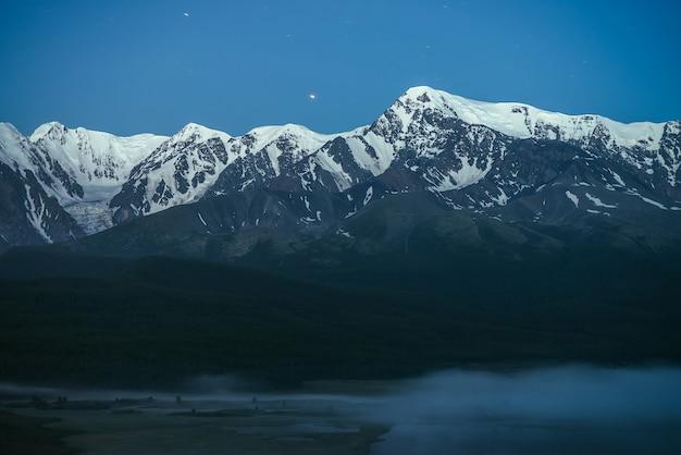 Atmosferyczny krajobraz z gęstą mgłą nad jeziorem i wielkim śnieżnym grzbietem górskim pod nocnym niebem. alpejskie krajobrazy z gęstą mgłą na górskie jezioro i duże pasmo górskie w nocy. szczyt śniegu w zmierzchu.