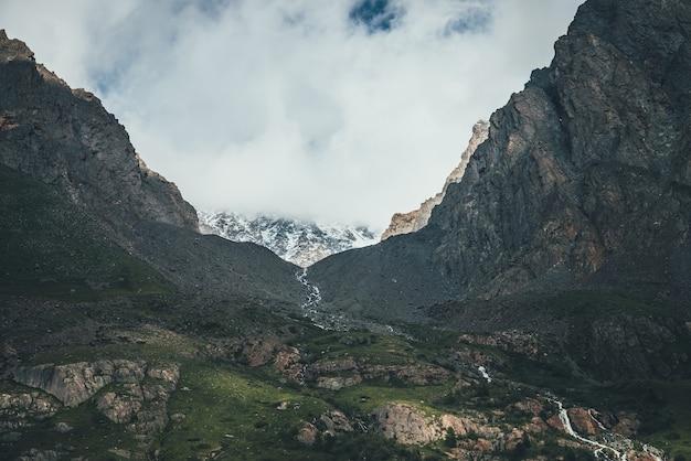 Atmosferyczny krajobraz z górskim strumieniem w wąskiej dolinie wśród wysokich gór skalistych. niskie chmury na górze ze śniegiem. piękna górska dolina z górskim potoku. niesamowita dolina wśród ostrych skał.