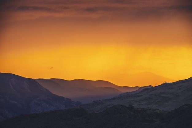 Atmosferyczny krajobraz z sylwetkami gór i wzgórz z drzewami na tle nieba pomarańczowego świtu. kolorowa sceneria przyrody z zachodem lub wschodem słońca o rozświetlonym kolorze. wynagrodzenie o zachodzie słońca.