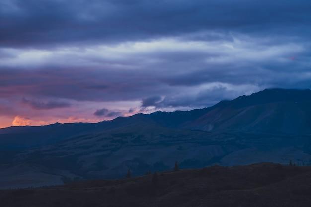Atmosferyczny krajobraz z sylwetkami gór na tle żywego nieba świtu. kolorowa sceneria przyrody z zachodem lub wschodem słońca pomarańczowy niebieski magenta fioletowy różowy kolor liliowy. wynagrodzenie o zachodzie słońca.