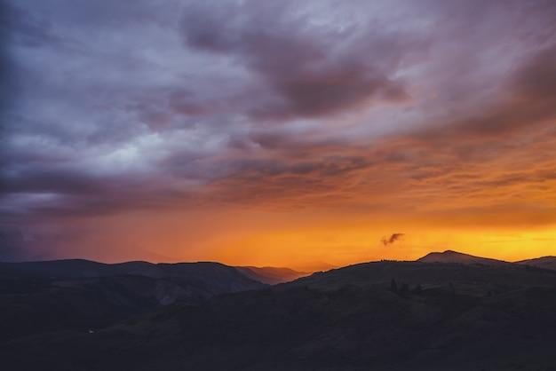 Atmosferyczny krajobraz z sylwetkami gór z drzewami na tle żywego pomarańczowego niebieskiego fioletowego nieba świtu. kolorowa sceneria przyrody z zachodem lub wschodem słońca o rozświetlonym kolorze. płatności o zachodzie słońca