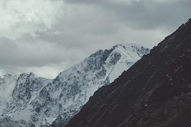 Atmosferyczny krajobraz z wielką ośnieżoną ścianą górską w chmurach. ponura górska sceneria z pokrytym śniegiem wysokim szczytem pod zachmurzonym niebem w wyblakłych odcieniach. śnieżny spiczasty szczyt i skały w ciemnych kolorach.