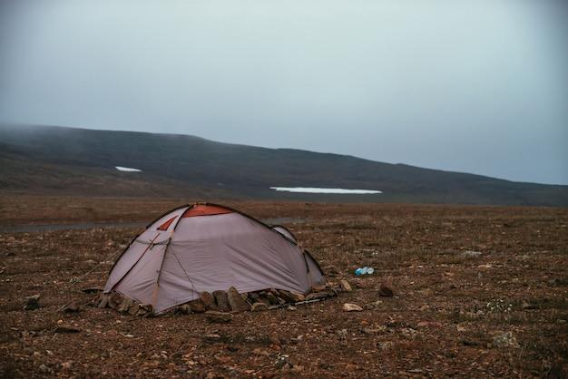 Atmosferyczny mglisty krajobraz górski z namiotem w kamiennym polu w dolinie wysokogórskiej w niskich chmurach. ponury mglisty krajobraz z namiotem na kamiennym wzgórzu wewnątrz chmury. namiot w niskich chmurach w dolinie górskiej.