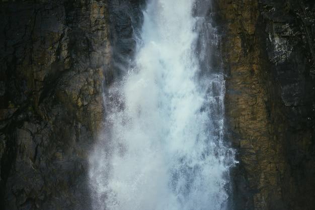 Atmosferyczny minimalny krajobraz z pionowym dużym wodospadem na skalnej ścianie górskiej. potężny duży wodospad w ciemnym wąwozie. tle przyrody o wysokiej pionowej turbulentnej spadającej wody na mokrych skałach.