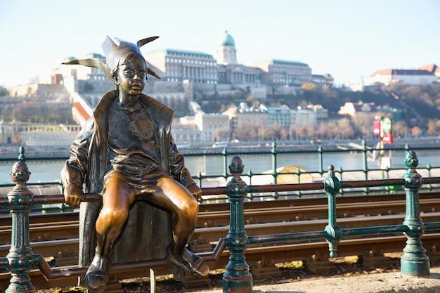 Atrakcje w budapeszcie. mała księżniczka siedząca przy szynach tramwajowych na peszcie, z zamkiem buda, charakterystycznym dla stolicy węgier. budapeszt, węgry.