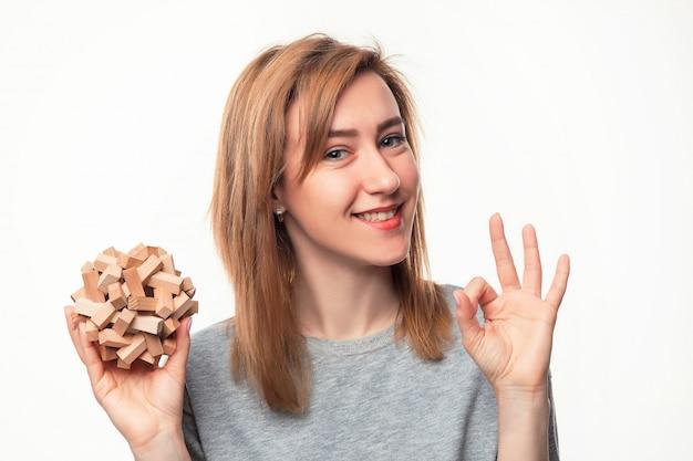 Atrakcyjna 24-letnia kobieta biznesu patrząc zmieszany z drewnianą łamigłówką.