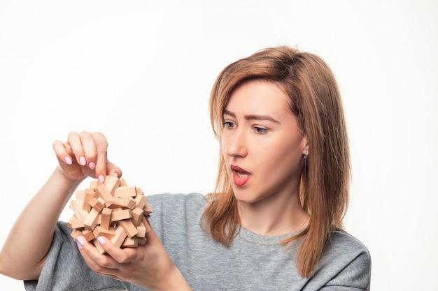 Atrakcyjna 24-letnia kobieta szuka mylić z drewnianą układanką.