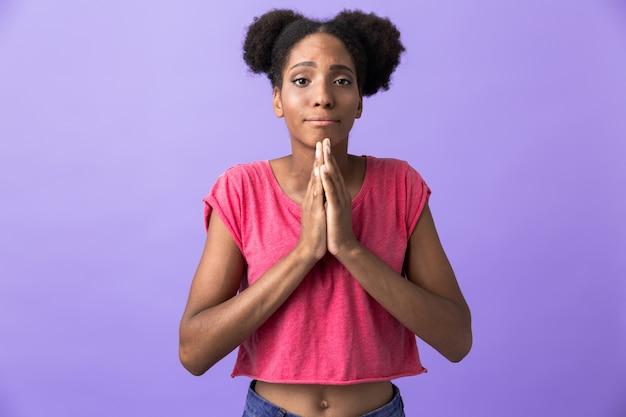 Atrakcyjna african american kobieta trzymając dłonie razem do modlitwy, odizolowane