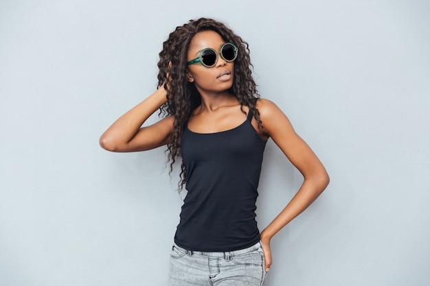 Atrakcyjna afro kobieta w okularach pozuje na szarej ścianie