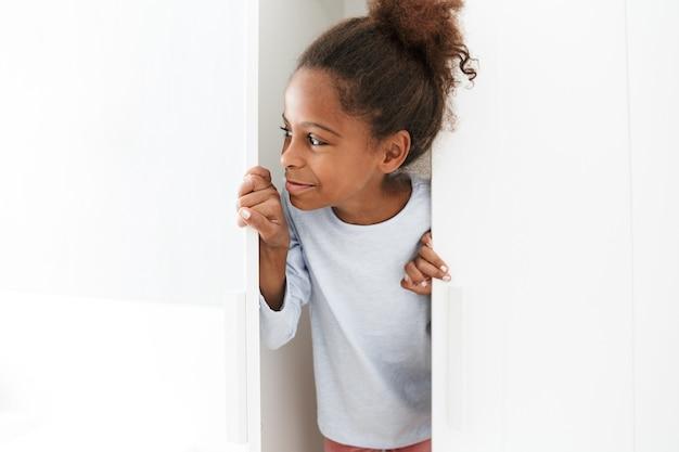 Atrakcyjna afroamerykańska mała dziewczynka uśmiecha się i bawi się w chowanego w szafie w domu