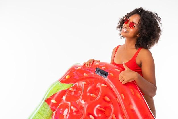 Atrakcyjna afrykańska dziewczyna w czerwonym seksownym kostiumie kąpielowym trzyma truskawkowy materac do pływania na białym