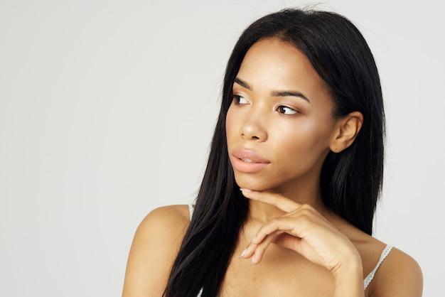 Atrakcyjna afrykańska kobieta trzymająca twarz modelka do makijażu