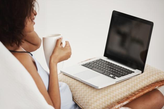 Atrakcyjna afrykańska kobieta uśmiecha się trzymający filiżankę patrzeje laptopu obsiadanie na krześle w domu.