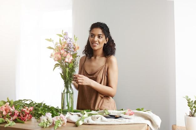 Atrakcyjna afrykańska kobiety kwiaciarnia ono uśmiecha się robić bukietowi kwiaty przy miejscem pracy nad biel ścianą.