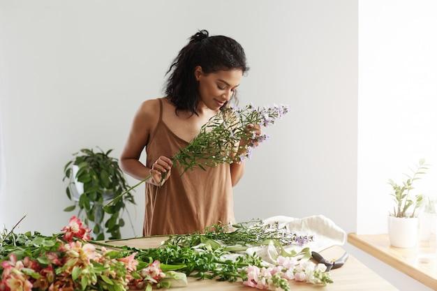 Atrakcyjna afrykańska żeńska kwiaciarnia ono uśmiecha się robić bukietowi przy miejscem pracy nad biel ścianą.