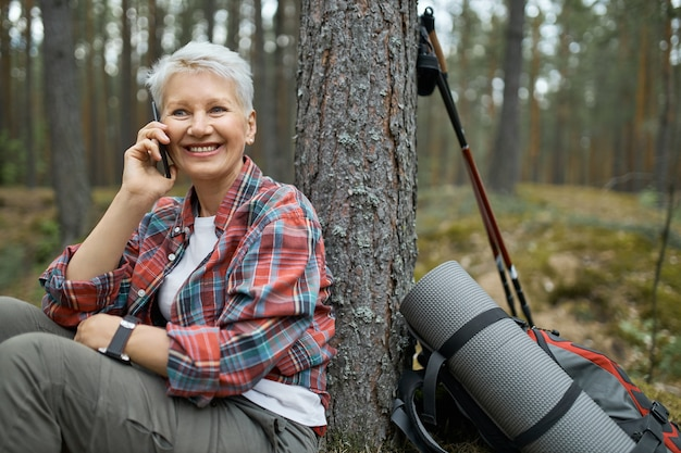 Atrakcyjna aktywna emerytka w kraciastej koszuli ma małą przerwę podczas wędrówki po lesie, siedzi pod drzewem, rozmawia z przyjacielem na telefonie komórkowym. podróżująca kobieta w średnim wieku, dzwoniących