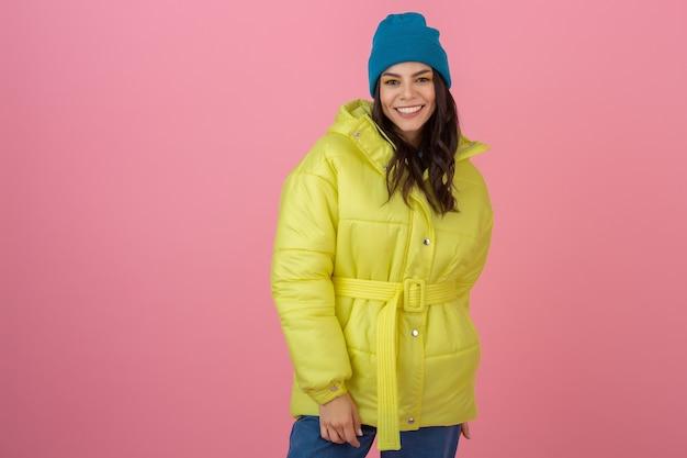 Atrakcyjna aktywna kobieta pozująca na różowej ścianie w kolorowej zimowej kurtce puchowej w jasnożółtym kolorze, uśmiechnięta zabawa, trend w modzie na ciepły płaszcz, szalony zszokowany, zaskoczony wyraz twarzy