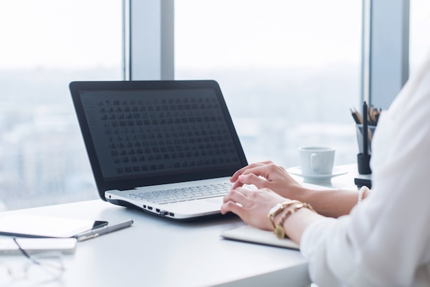Atrakcyjna asystentka pracująca, pisząca na maszynie, z komputerem przenośnym, skoncentrowana