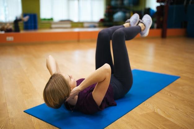 Atrakcyjna atleta młoda kobieta robi ćwiczeniu. wewnątrz.
